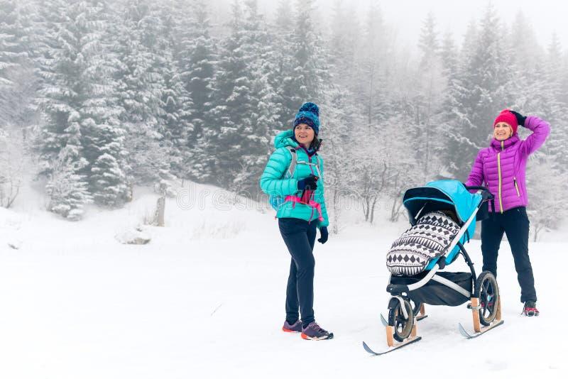 Famille heureuse en montagnes Mère avec le promeneur de bébé appréciant le MOIS image libre de droits