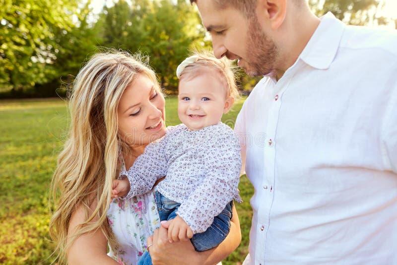 Famille heureuse en parc en automne d'été photo stock
