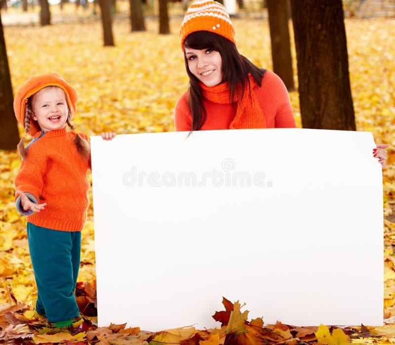 Famille heureuse, enfant sur la lame orange d'automne, drapeau photo libre de droits