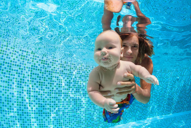 Famille heureuse - engendrez, petite eau du fond de piqué de fils dans la piscine photo stock