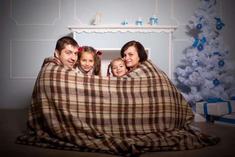 Famille heureuse enveloppée dans le plaid photos stock