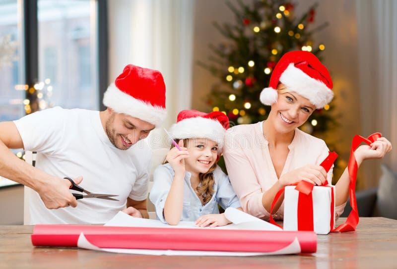 Famille heureuse enveloppant des cadeaux de Noël à la maison photo stock