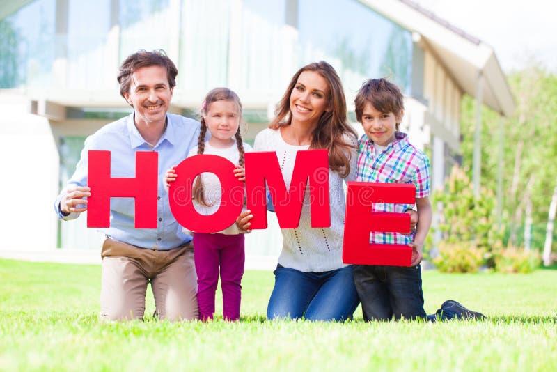 Famille heureuse et lettres à la maison photographie stock libre de droits