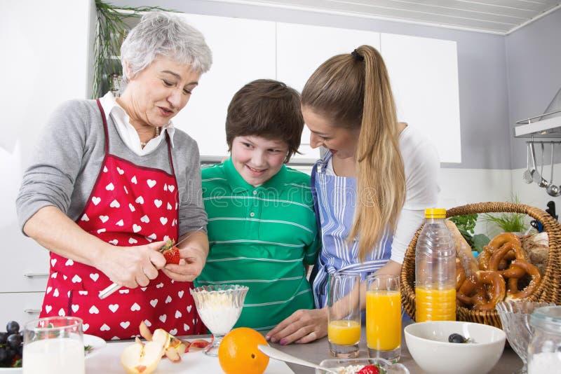 Famille heureuse faisant cuire ainsi que la grand-mère photo libre de droits