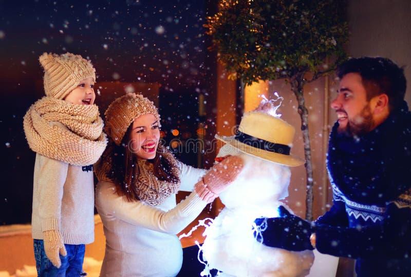 Famille heureuse faisant le bonhomme de neige dans la lumière de soirée sous la neige d'hiver photographie stock libre de droits