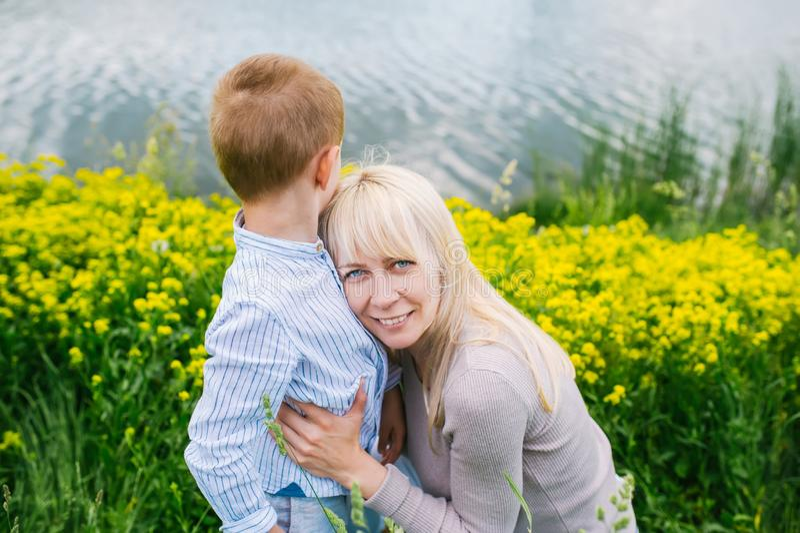 Famille heureuse : Fils et mère s'asseyant sur l'herbe près du lac image stock