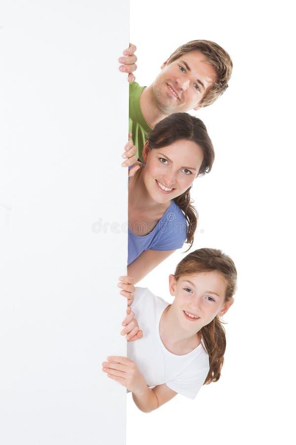 Famille heureuse jetant un coup d'oeil du panneau d'affichage vide image stock