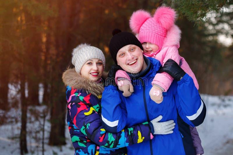 Famille heureuse, jeunes couples et leur fille passant le temps extérieur en hiver image stock