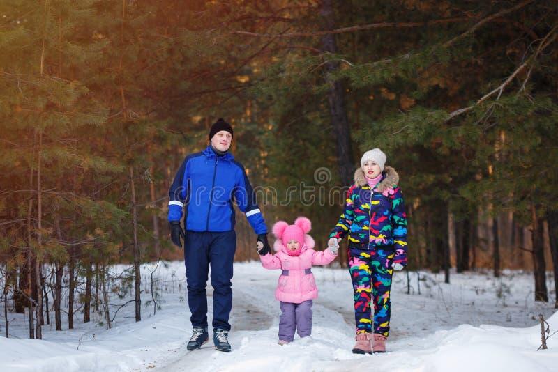 Famille heureuse, jeunes couples et leur fille passant le temps extérieur en hiver image libre de droits
