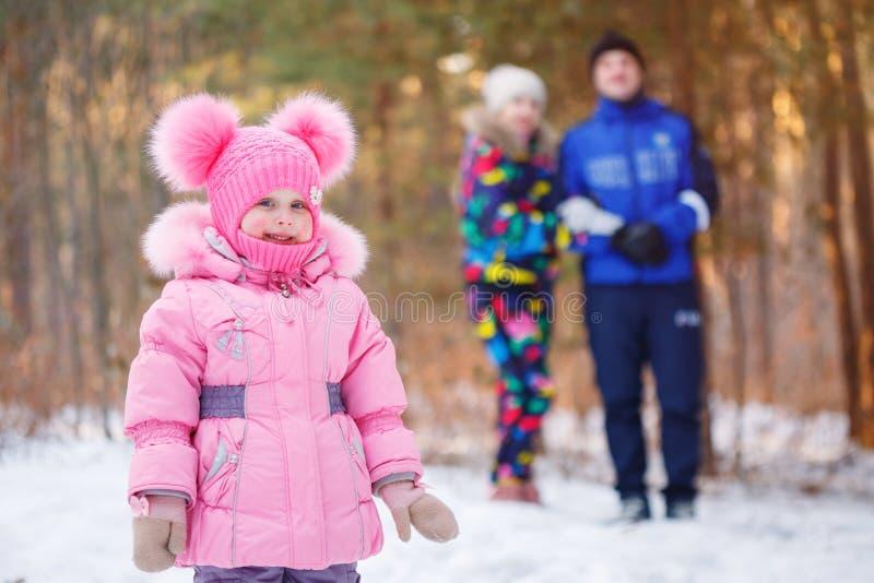Famille heureuse, jeunes couples et leur fille passant le temps extérieur en hiver photographie stock libre de droits