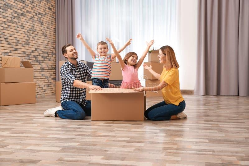 Famille heureuse jouant avec la boîte en carton dans leur nouvelle maison image libre de droits