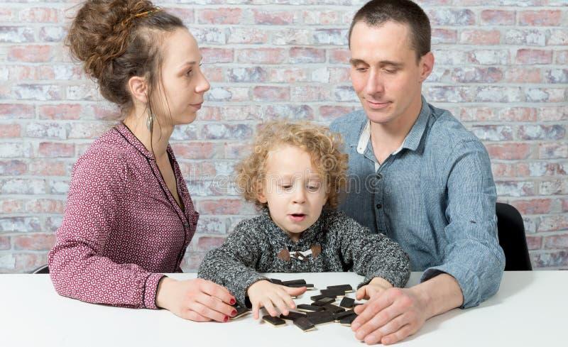 Famille heureuse jouant des dominos photos stock