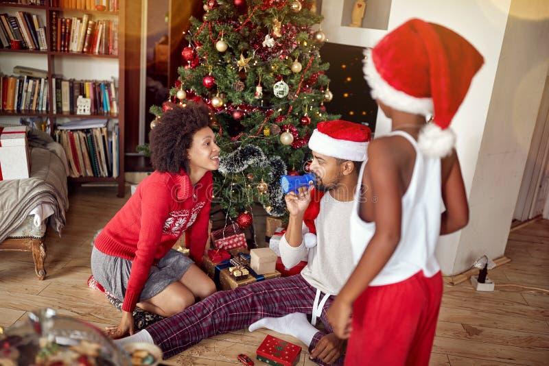 Famille heureuse jouant devant un arbre de Noël décoré photos libres de droits