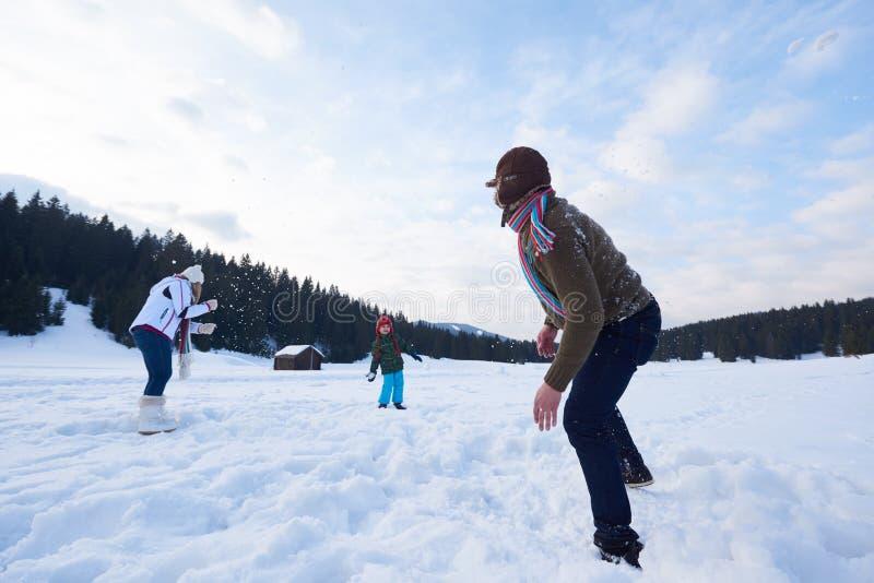 Famille heureuse jouant ensemble dans la neige à l'hiver photographie stock