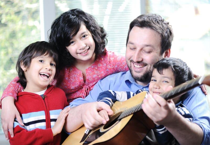 Famille heureuse jouant la guitare ensemble image libre de droits