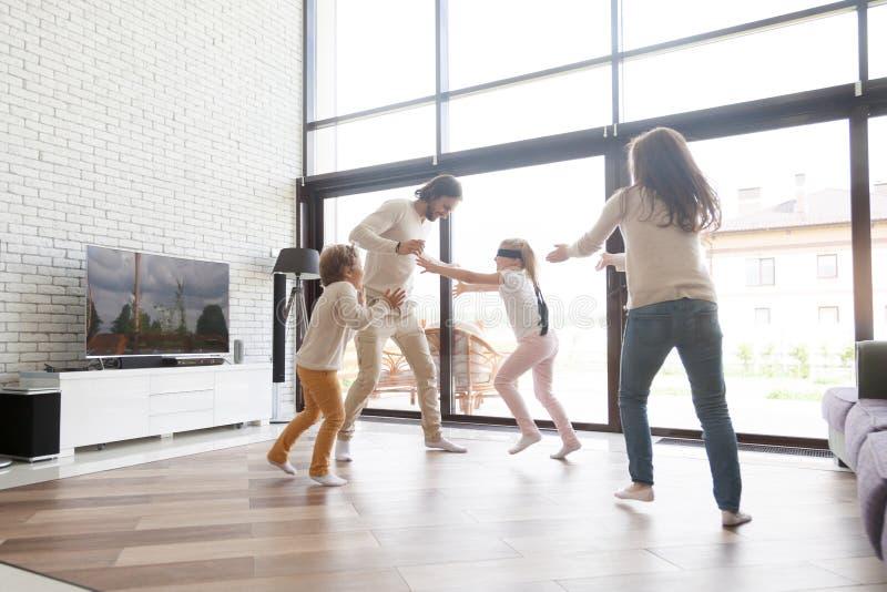 Famille heureuse jouant le cache-cache à la maison photographie stock