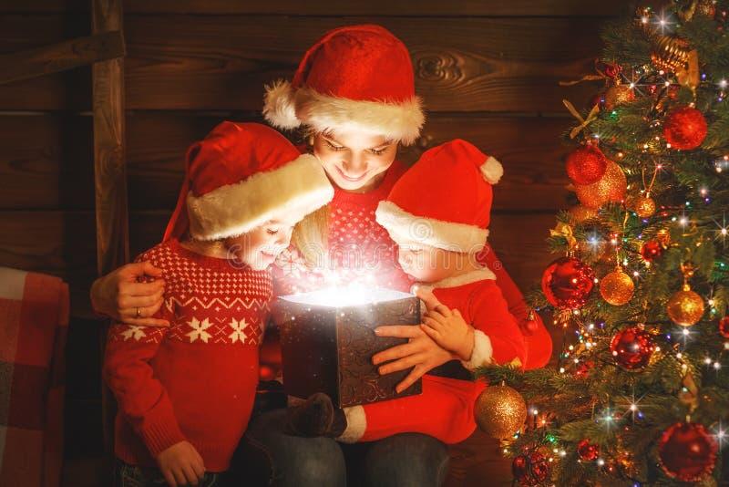 Famille heureuse le réveillon de Noël la mère et les enfants découvrent un mA photographie stock libre de droits