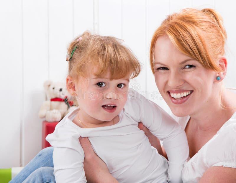 Famille heureuse :  mère et fille souriant à l'appareil-photo - strawberr photo libre de droits