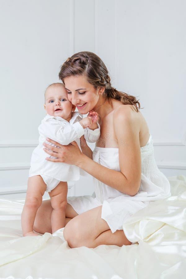 Famille heureuse, mère et son fils de bébé jouant et smilling sur le Ba photo stock