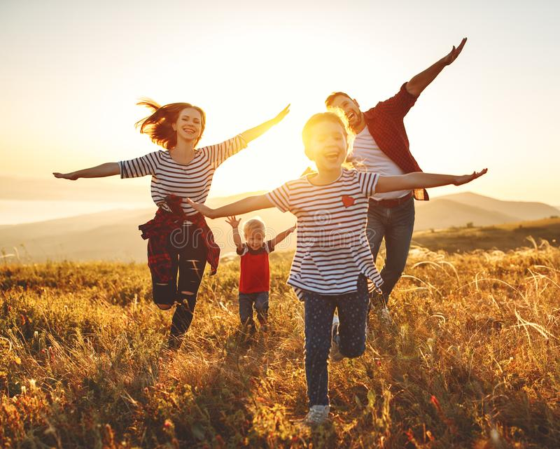 Famille heureuse : mère, père, enfants fils et fille sur le coucher du soleil image libre de droits