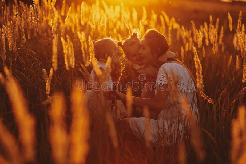 Famille heureuse, maman et deux filles La mère joue avec sa fille sur la rue dedans au coucher du soleil Concept de la famille photographie stock libre de droits