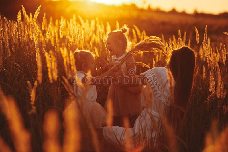 Famille heureuse, maman et deux filles La m?re joue avec sa fille sur la rue en parc au coucher du soleil photos libres de droits