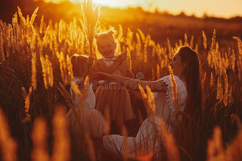 Famille heureuse, maman et deux filles La m?re joue avec sa fille sur la rue en parc au coucher du soleil photographie stock