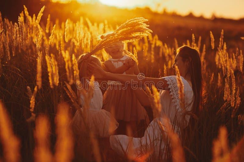 Famille heureuse, maman et deux filles La m?re joue avec sa fille sur la rue en parc au coucher du soleil images stock