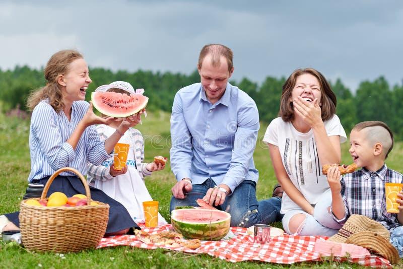 Famille heureuse mangeant la pastèque à un pique-nique Pique-nique dans le pr? ou le parc Jeunes amis et leurs enfants en nature photographie stock