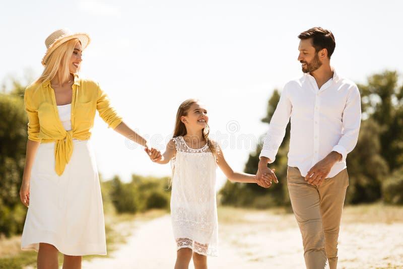 Famille heureuse marchant dans la campagne et ayant l'amusement photographie stock libre de droits