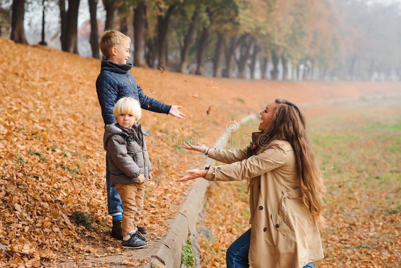 Famille heureuse marchant en parc d'automne Mère et enfants jouant avec les feuilles tombées Amour, relations, famille, saison et photo libre de droits