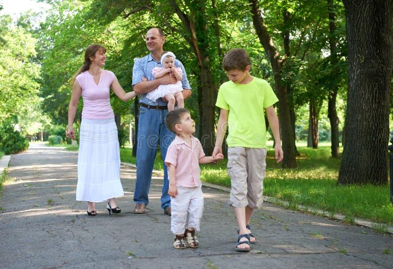 Famille heureuse marchant en parc de ville, groupe de cinq personnes, saison d'été, enfant et parent images stock