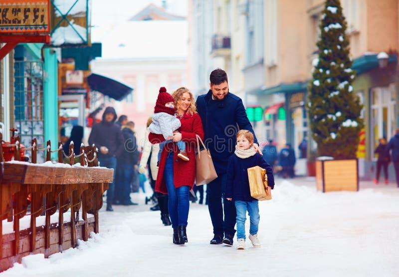 Famille heureuse marchant ensemble à la rue neigeuse de ville pendant l'hiver photographie stock