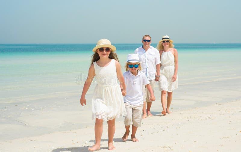 Famille heureuse marchant le long d'une plage images libres de droits