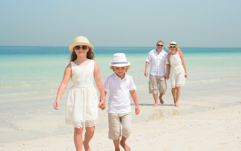 Famille heureuse marchant le long d'une plage photographie stock libre de droits