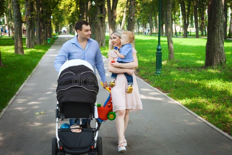 Famille heureuse marchant le long des allées en parc photos libres de droits