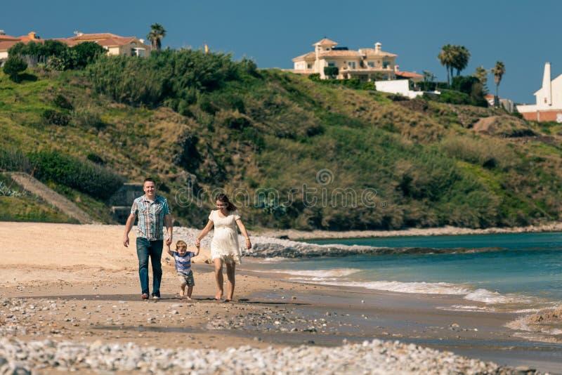 Famille heureuse marchant sur la côte en Espagne photographie stock libre de droits