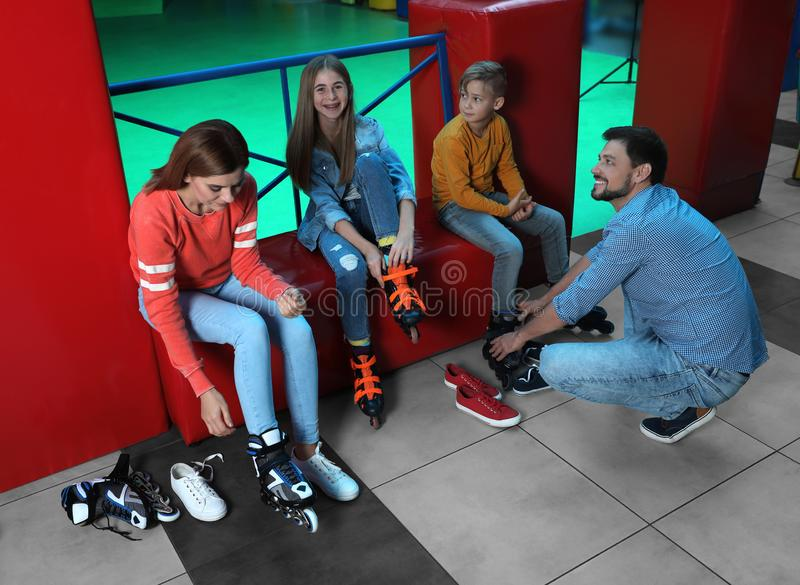Famille heureuse mettant sur des patins de rouleau photographie stock libre de droits