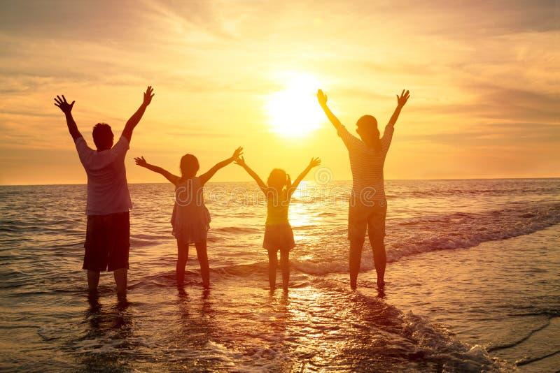 Famille heureuse observant le coucher du soleil sur la plage photo stock