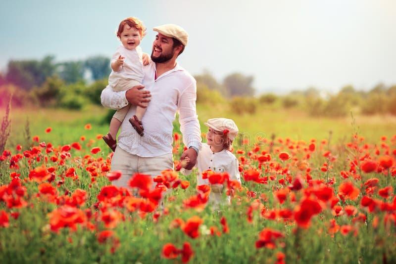 Famille heureuse, père avec des enfants jouant dans le domaine de fleur de pavot au jour d'été images stock