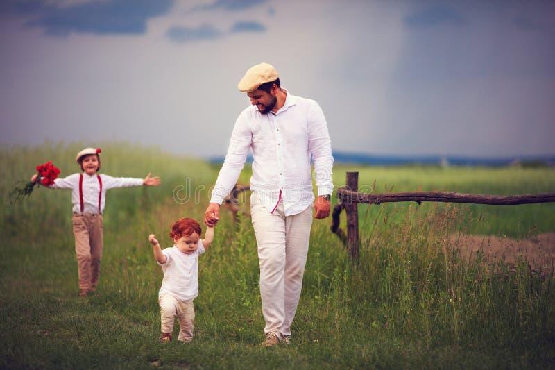 Famille heureuse, père avec des enfants marchant par le champ de campagne au jour d'été photographie stock libre de droits