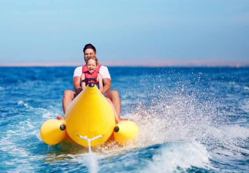 Famille heureuse, père avec plaisir et fils ayant l'amusement, montant sur le bateau de banane pendant des vacances d'été images stock