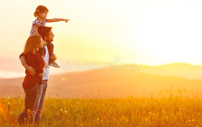 Famille heureuse : père de mère et fille d'enfant sur le coucher du soleil image stock