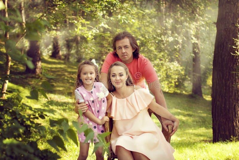 Famille heureuse - père, mère et fille se reposant en été dedans image stock