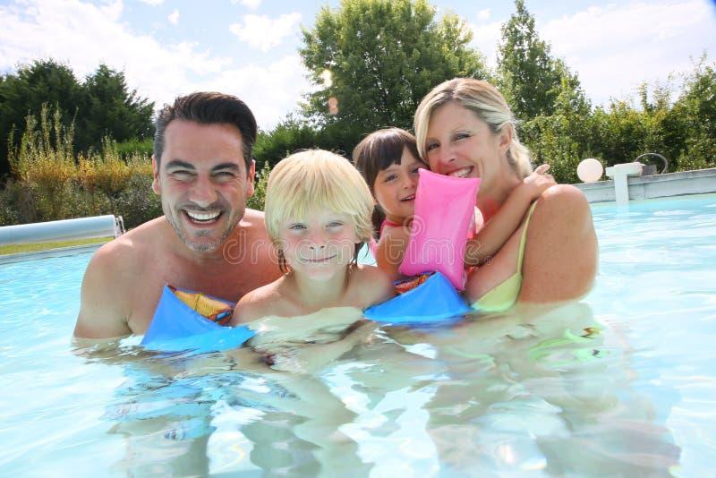 Famille heureuse passant le bon temps dans la piscine images libres de droits