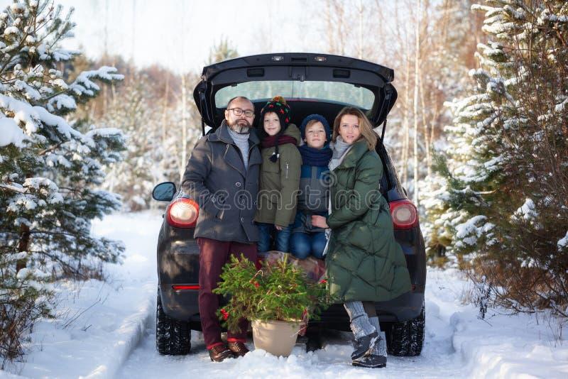 Famille heureuse près de voiture noire snowly au jour d'hiver Vacances de vacances de concept photos libres de droits