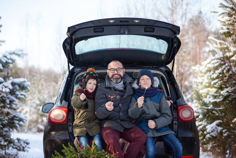 Famille heureuse près de voiture noire snowly au jour d'hiver Vacances de vacances de concept image libre de droits
