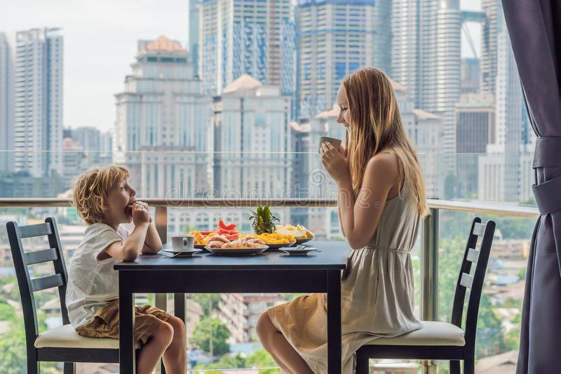 Famille heureuse prenant le petit déjeuner sur le balcon Table de petit déjeuner avec le fruit et le pain de café croisant sur un photos stock