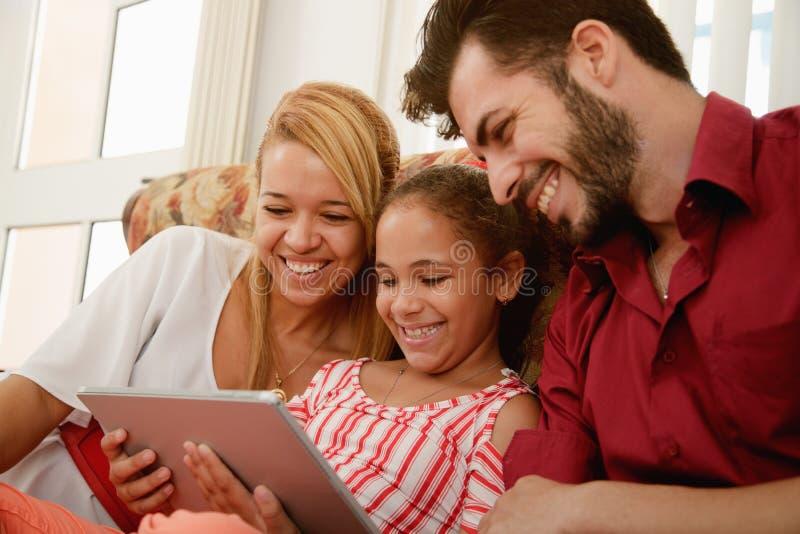 Famille heureuse riant regardant la vidéo sur la tablette photo stock