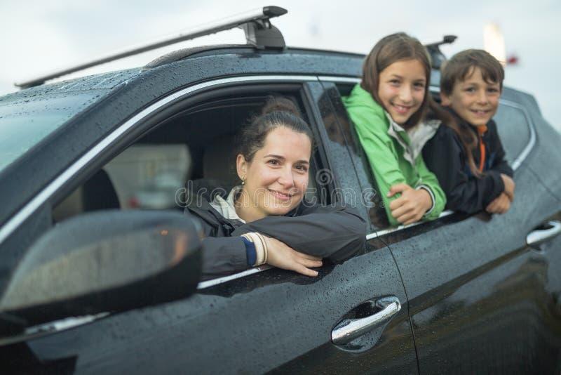 Famille heureuse s'asseyant dans la voiture photo stock